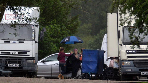 Downton drizzle: Maggie Smith is shielded from the rain between takes in Scotland