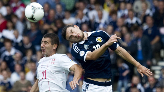 Scotland's Robert Snodgrass (right) rises in the air with Aleksandar Kolarov