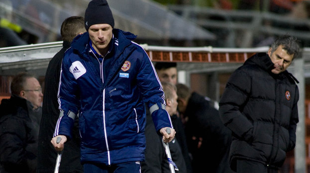 Dundee Utd coach Darren Jackson (right) looks on as Marius Zaliukas heads for the dressing room on crutches.