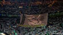 The Green Brigade unveil a banner before the match
