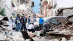 People survey the damage along a street